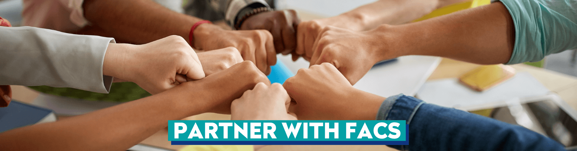 group of people putting fists together as a team