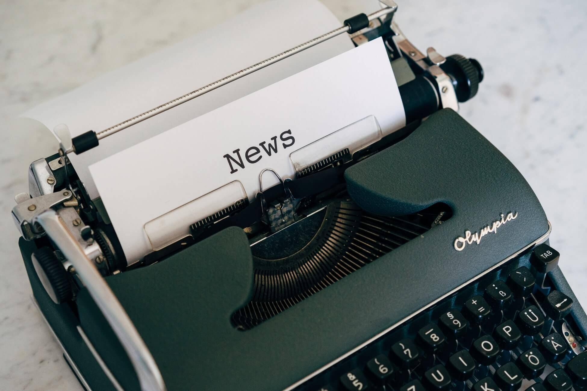 """a typewriter with a paper that says """"news"""""""