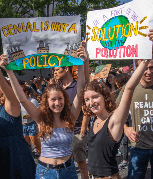 young women holding signs about climate change